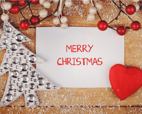 Merry Christmas written on paper with snow and decorations around it