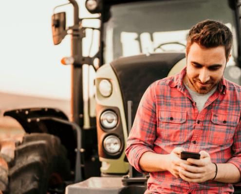 Young man looking at smart phone while leaning on a tractor