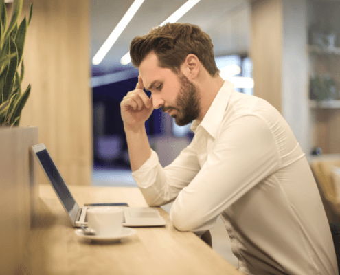 Man with coffee concentrating on laptop