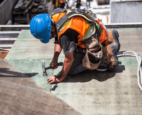 Construction worker hammering on a roof top