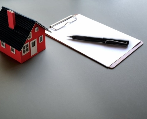 Model of small house beside clipboard