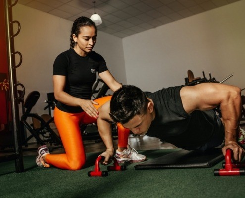 Man doing pushups with female trainer