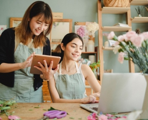 Two young women working on laptop and iPad in a flower shop