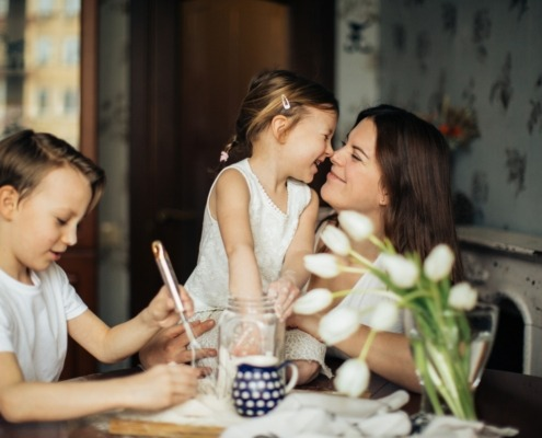 Young women rubbing noses with young child and another child sitting with them at the table
