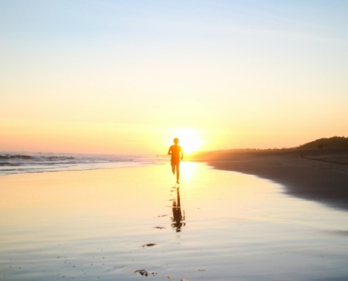 Man running on the beach with sun setting behind him