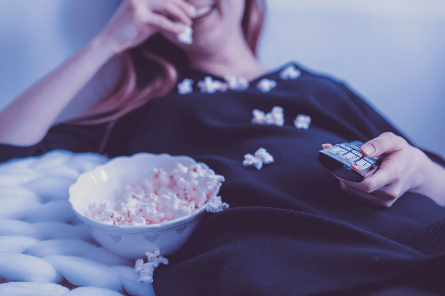 Woman lying back while eating popcorn with remote in her hand