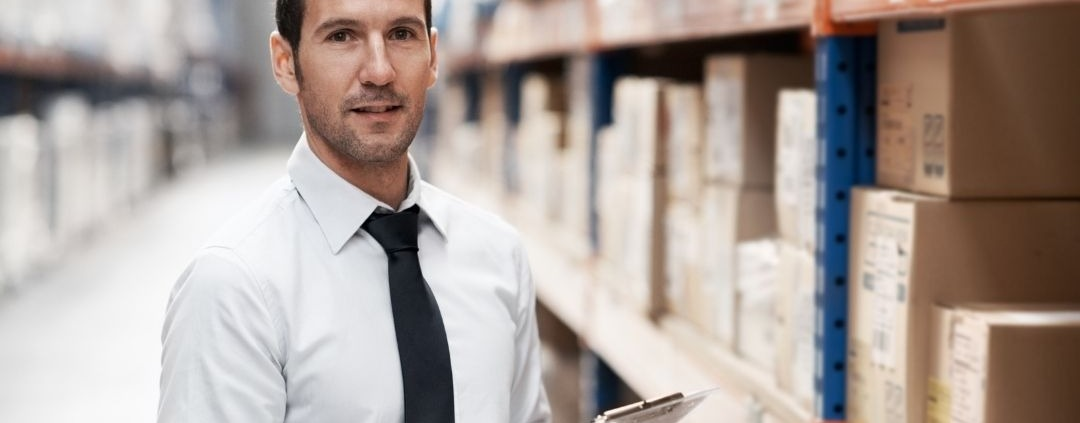 Man with clipboard standing in front of stock shelves