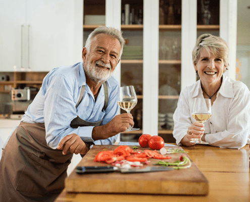 Older couple with glasses of wine in the kitchen