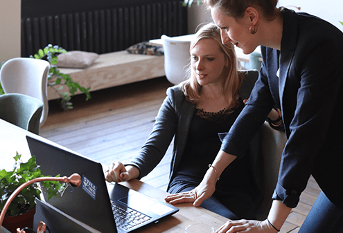 Two business women looking at laptop